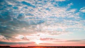 Timelapse, een heldere zonsondergang met lekke wolken en een voorbijgaande passagierstrein stock videobeelden
