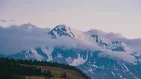 Timelapse El sol fija y las nubes cubren el pico de la nieve Puesta del sol del paisaje en las montañas metrajes