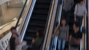 Timelapse of escalators with people in trade centre. Timelapse shot of people riding up and down escalators in shopping mall stock footage