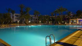 Timelapse evening light under water swimming pool and palm trees on background. Timelapse evening light under water swimming pool and palm trees in resort hotel stock footage
