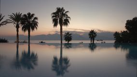 Timelapse of evening on resort. Pool, palms and scene with sea and mountains stock video