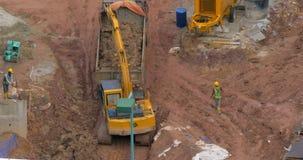 Timelapse of excavator loading truck. KUALA LUMPUR, MALAYSIA - NOVEMBER 05, 2015: Timelapse shot of excavator loading dump truck with ground. Works on stock footage