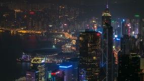 Timelapse för Hong Kong stadshorisont på natten med Victoria Harbor och skyskrapor som är upplysta vid ljus över beskådat vatten arkivfilmer
