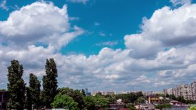 Timelapse of fast moving clouds over the city. Trees and apartment buildings are in the backgorund stock footage