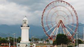 Timelapse Ferris wheel and Batumi lighthouse on the Batumi Seafront Promenade in the cloudy day, Adjara stock footage
