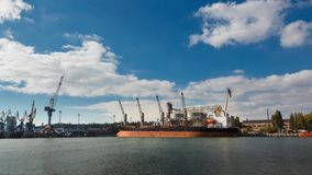 Timelapse of grain terminal at seaport on sunny day. Cereals bulk transshipment to vessel loading grain crops on bulk. Timelapse of grain terminal at seaport on stock footage