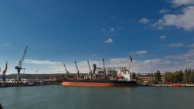 Timelapse of grain terminal at seaport on sunny day. Cereals bulk transshipment to vessel loading grain crops on bulk. Timelapse of grain terminal at seaport on stock video footage