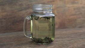 Timelapse of a a green tea brewing process on a wooden background. stock video footage