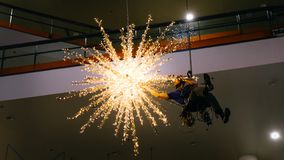 Timelapse industrial climber hangs Christmas decorations - connects a large garland. In the mall stock images