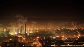 Timelapse 4k da zona industrial da cidade da noite Fumo das tubulações da fabricação Tráfego das casas e de carro do aeria de Res filme