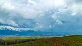 timelapse 4K El invierno se nubla sobre los campos de la primavera, colinas de Tien Shan occidental almacen de metraje de vídeo