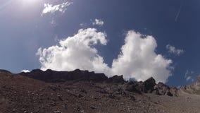 Timelapse of clouds moving on blue skies behind rocks