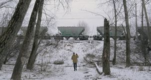 Timelapse of man shooting video of cargo train passing by. Timelapse shot of a man stocker with camera on tripod shooting video of passing freight train in stock video