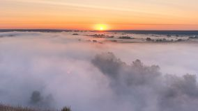 Timelapse mist curling over river and meadow on sunrise background stock footage