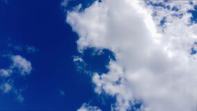 Timelapse Movement of white cumulus clouds on bright blue sky 4K