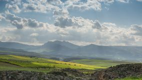 Timelapse with moving clouds in Atlas mountains Morocco. Timelapse with moving clouds over green fields in Atlas mountains Morocco stock video