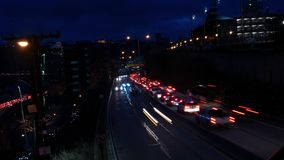 Timelapse of multi lane highway traffic leaving or entering city area around a mountain.  stock video