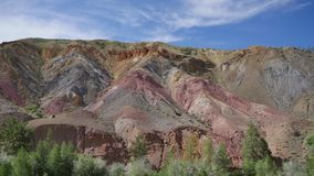 Multicolored mountains. Timelapse. Red and yellow hill. Blue sky with light clouds. Timelapse. The multicolored hill is looking like Mars. It`s a sunny and a stock video footage