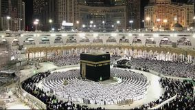 Timelapse of Muslim pilgrims perform evening prayer. Timelapse of Muslim pilgrims in white ihram cloth from lines facing the Kaaba and perform evening prayer