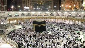 Timelapse of Muslim pilgrims perform evening prayer. Timelapse of Muslim pilgrims in white ihram cloth from lines facing the Kaaba and perform evening prayer stock video