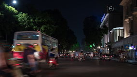 Timelapse of night city, seen busy road with passing cars, motorcycles and cyclists stock footage