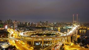 Timelapse night heavy traffic on highway interchange,Brightly lit cityscape. Aerial freeway busy city rush hour heavy traffic jam highway Shanghai at night stock video footage