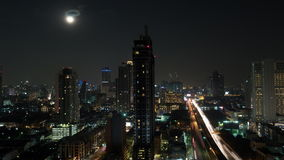 Timelapse of night illuminated Bangkok. Timelapse shot of the moon rising in night Bangkok. Night cityscape of Thailand capital. View to the illuminated stock video
