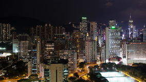 Timelapse of night illuminated Hong Kong. Timelapse panning shot of Hong Kong at night. City with illuminated buildings, roads and football fields stock footage