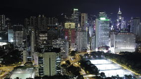 Timelapse of night life in Hong Kong. Timelapse shot of illuminated Hong Kong. Night city view with concrete jungle, road interchange and football fields stock video