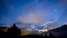 Timelapse night sky stars and moon across fast clouds with mountain background