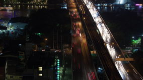 Timelapse of night traffic across the bridge, Bangkok. Timelapse high angle shot of red and white streams of moving transport on the bridge across the channel in stock video footage