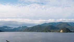 Timelapse, o lago Como em um fundo das vilas nas montanhas e o céu azul com nuvens de cirro movem-se rapidamente através do video estoque