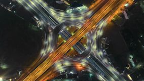 Timelapse Of Night City Traffic On 4-way Stop Street Intersection Circle Roundabout In Bangkok, Thailand. 4K UHD Horizontal Aerial Royalty Free Stock Photo