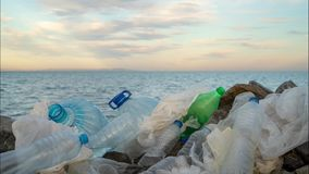 Timelapse. Plastic bottles in a polluted. Clouds background