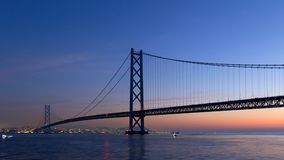 Timelapse - ponte de Akashi Kaikyo e o movimento do navio no alvorecer video estoque