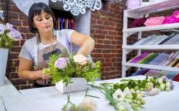 Timelapse professional florist arranging flower composition in wooden box in floral design studio. Caucasian female master in apron creating floral design stock image