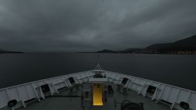 A Ship Departs Stokmarknes, Norway. A timelapse recording looking over the bow of a ship as it departs the town of Stokmarknes, Norway stock video