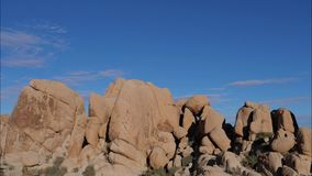 Time Lapse Of Rocky Boulders Sand Color And Blue Sky, Joshua Tree National Park. Timelapse, rocks in the form of rounded boulders and stones, sand color and blue stock video