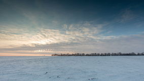Timelapse. Russia. The movement of the clouds at sunset in the snowy steppe in winter.