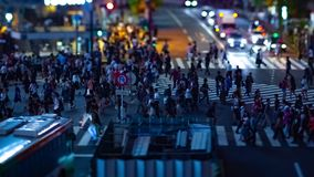 A timelapse of the scramble crossing at the neon town in Shibuya Tokyo tilt shift zoom. A timelapse of the scramble crossing at the neon town tilt shift zoom stock video footage