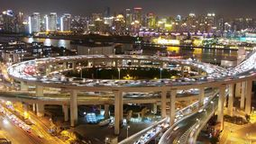 Timelapse shanghai traffic on highway interchange at night,urban cityscape. Aerial freeway busy city rush hour heavy traffic jam highway Shanghai at night stock video