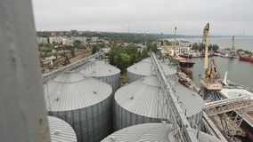 Timelapse of ship loading grain crops on bulk freighter via trunk to open cargo holds at silo terminal in seaport. Panorama of ship loading grain crops on bulk stock footage