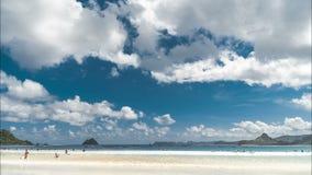 Timelapse si rannuvola la spiaggia di Pantai Selong Belanak con i lotti dei principianti dei surfisti all'isola di Lombok, Indone stock footage
