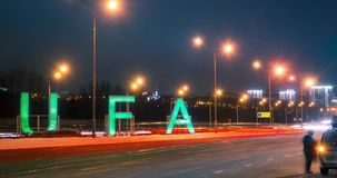 Timelapse of sign Ufa and transport traffic on main road into city in the winter night. Bashkortostan, Russia. stock footage