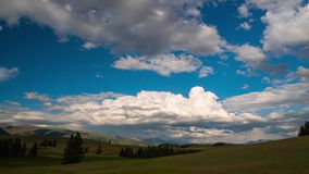 Timelapse Solnedgången solsidorna, vita moln svävar ovanför de gröna kullarna i den blåa himlen Berglandskap, sommar arkivfilmer