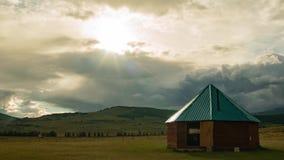 Timelapse Solnedgången, soluppsättningarna och sken en ljus stråle av det traditionella etniska nationella huset, gråa moln sväva lager videofilmer
