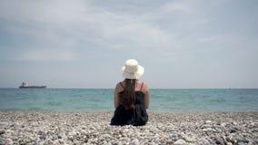 Timelapse som skjuter en flicka i en ljus klänning och en vit hatt som sitter på stranden och beundrar det härliga landskapet arkivfilmer