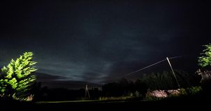 Timelapse of stars over trees at winter night then clouds coming on dark sky. stock video