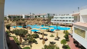 Timelapse of hotel resort with blue swimming pool, umbrellas and sunbeds in Egypt