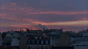 Timelapse of sunrise over Paris in winter. Timelapse of sunrise over Paris roofs in winter with clouds and smoking chimneys - France stock video footage